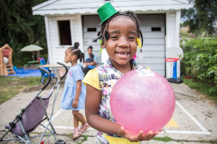 Little girl smiling and holding a ball