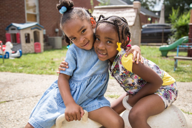 Two girls smiling on a playground