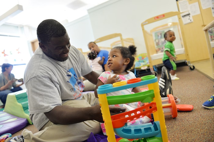 man and small girl playing with toys in preschool classroom